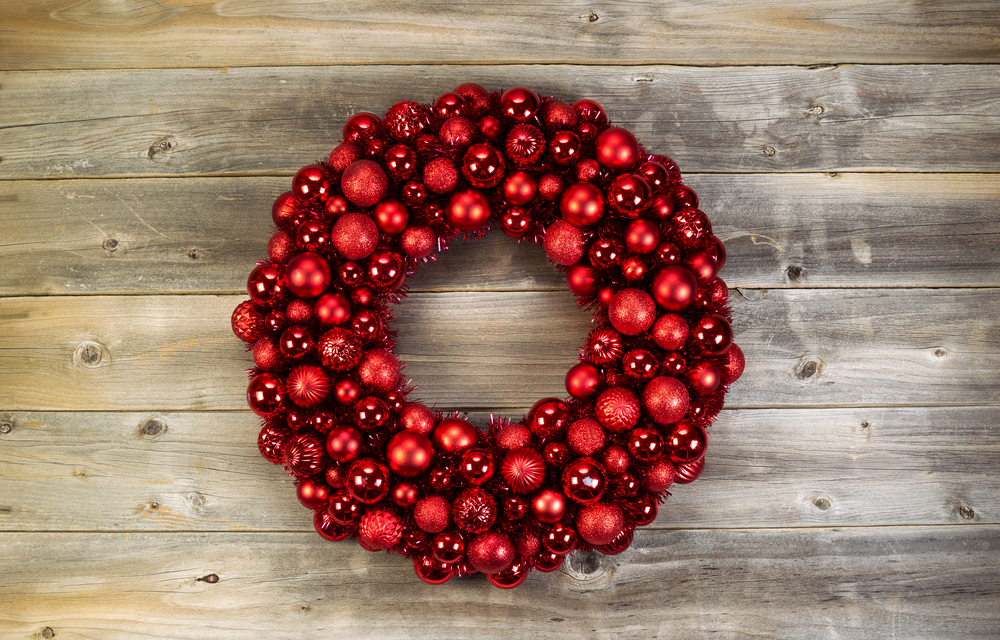 Top view of a large Christmas Wreath made with red ornaments on rustic wood