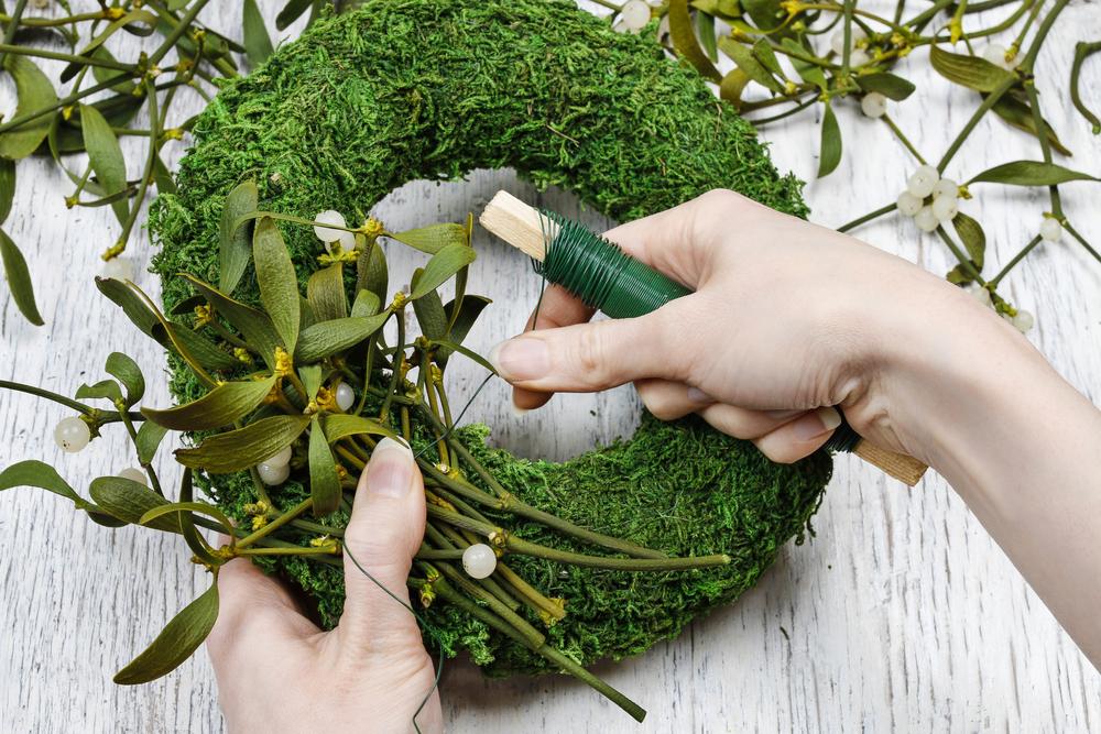 Florist at work: woman making mistletoe wreath. Christmas decoration