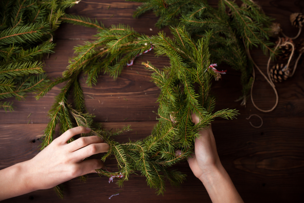 Making Christmas wreath with hands on brown wooden background